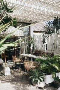Woven chairs on a balcony next to tropical plants - might just have the makings of a good apartment..