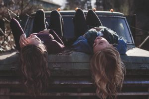 Teens lying on a hood of an old car - it's your job as a parent to help them cope with the move.