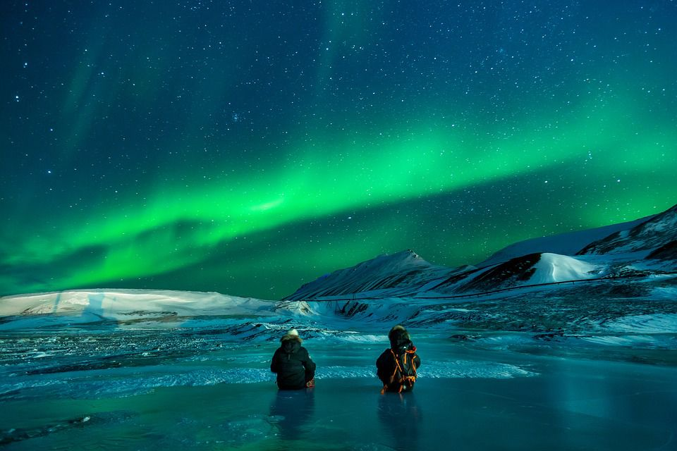 Two people on frozen lake, watching Aurora Borealis - enjoy the many beauties Alaska has to offer.