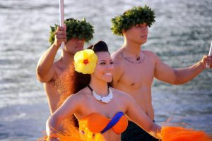 Two Hawaiian men and a Hula girl smiling.