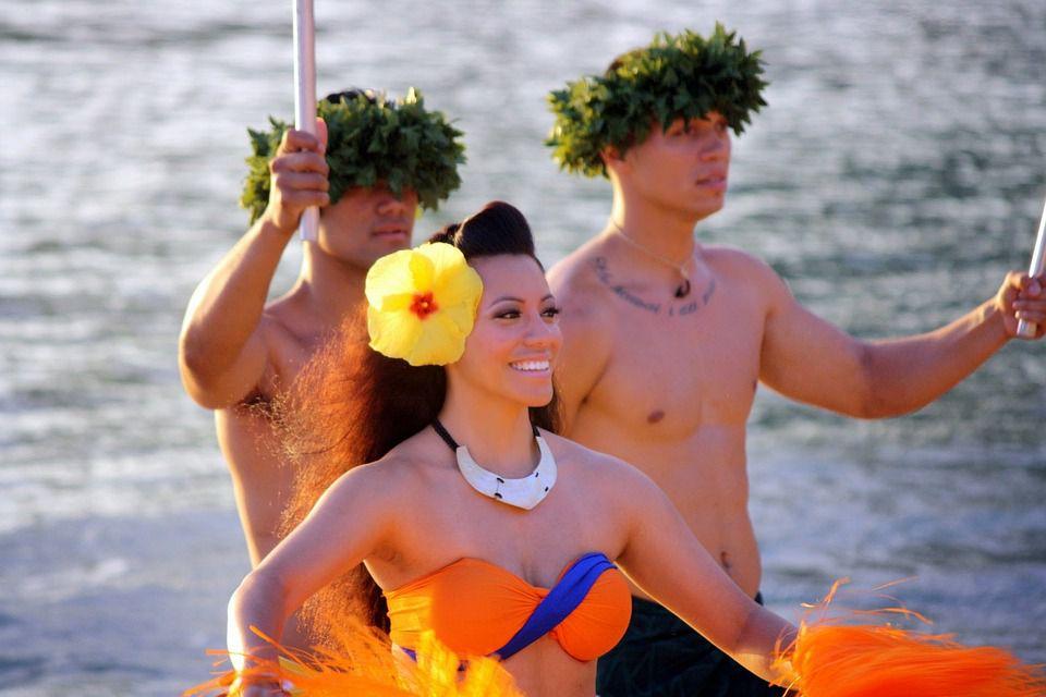 Two Hawaiian men and a Hula girl smiling.