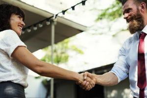 Woman with black hair and white shirt shaking hands with a bearded businessman