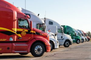 Different-colored moving trucks, waiting for one of the reasons for relocation to come around.