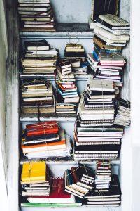 Messy bookshelf. - something that renting a self storage unit can fix.