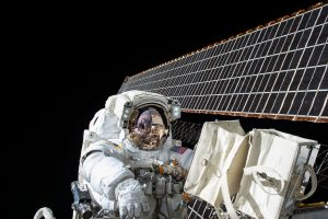 An astronaut in a spacewalk with a solar panel behind him
