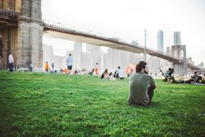 Man sitting on gree surface, enjoying the view of the Brooklyn Bridge after long distance moving companies New York City have helped him settle in.