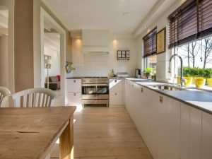 A white kitchen, empty apart from counters, sinks and a stove.