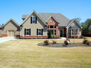 A gray suburban home with a large front yard.