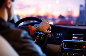 A man driving a car during dusk, as an example of having moving insurance.