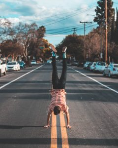 Man doing a handstand in the middle of a road