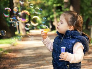 A small girl blowing soap bubbles in a park.