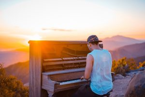 Man playing a piano into the sunset
