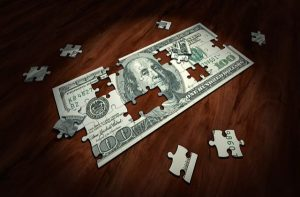 A puzzle with an image of a hundred dollar bill, on a wooden surface.