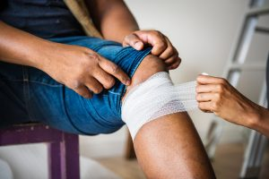 A doctor wrapping a man's leg with bandage