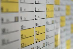 A wall calendar with yellow and white dates.