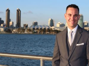 A businessman standing smiling with the San Diego skyline in the background.