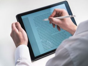 A person going tracing a text on a tablet with a pen.