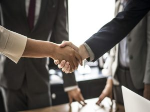 Two people shaking hands in a meeting.