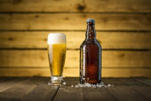 A beer bottle next to a glass of beer, against a wooden background.
