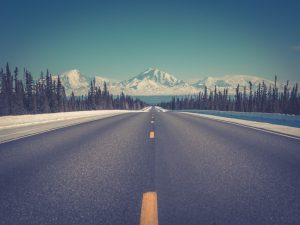 A road in Alaska, stretching towards snowy mountains.