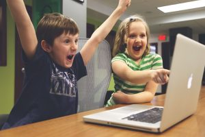 Two kids looking at a laptop and celebrating.