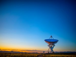 A satellite array in a field in New Mexico, during sundown.