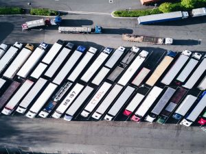 Two rows of moving trucks on a parking lot, seen from above.