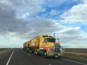 A yellow moving truck driving down a highway.