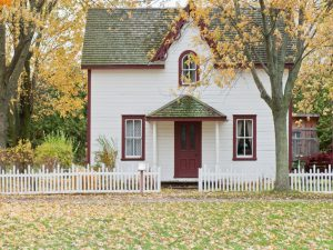 A suburban home surrounded by autumn trees, and a white picket fence.