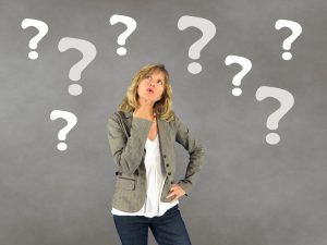Woman thinking surrounded by question marks