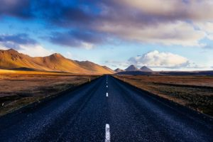 black concrete road with distance to mountains