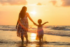 A mother enjoying the sunset with her child