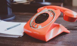An orange phone next to a notebook.