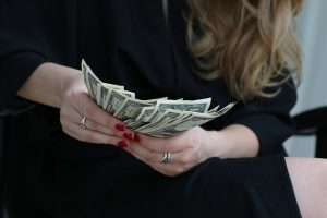 Women counting money - something you should do when moving from Des Moines to Las Vegas