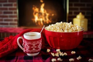 cup of tee and popcorn near the fireplace