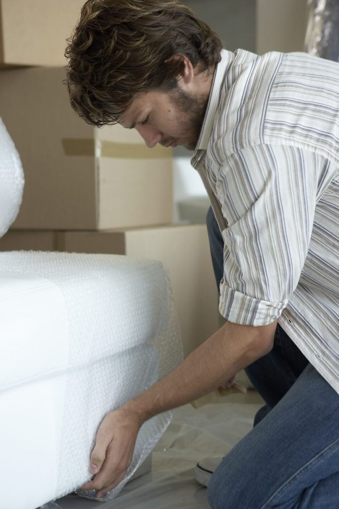 Man wrapping furniture in bubble wrap
