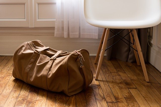 Brown bag on the floor and a white chair