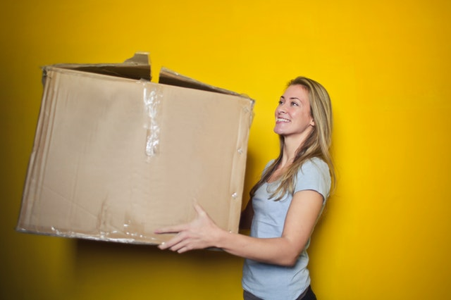 Woman in grey shirt holding a box