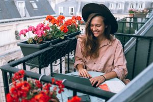 woman working on a laptop on a balcony