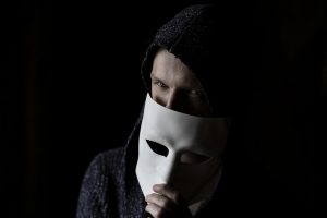 A scammer holding an Anonymous mask