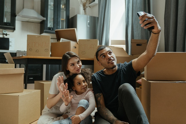 Family sitting in room full of moving boxes