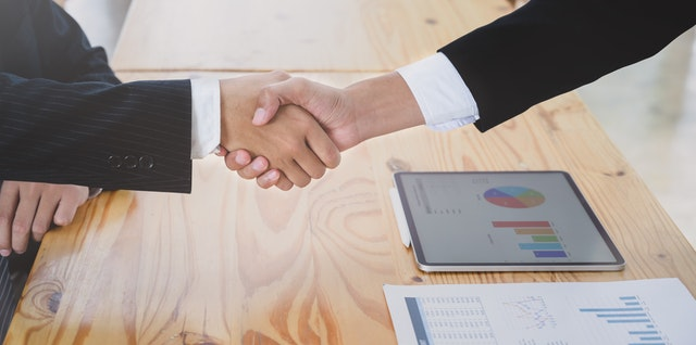 Two persons shaking hands after reading about the Economic Impact Study of the Moving & Storage Industry