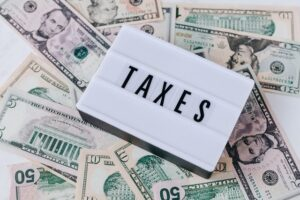 word taxes on a pile of US money