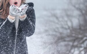 Girl blowing snowflakes from her gloves in a blizzard