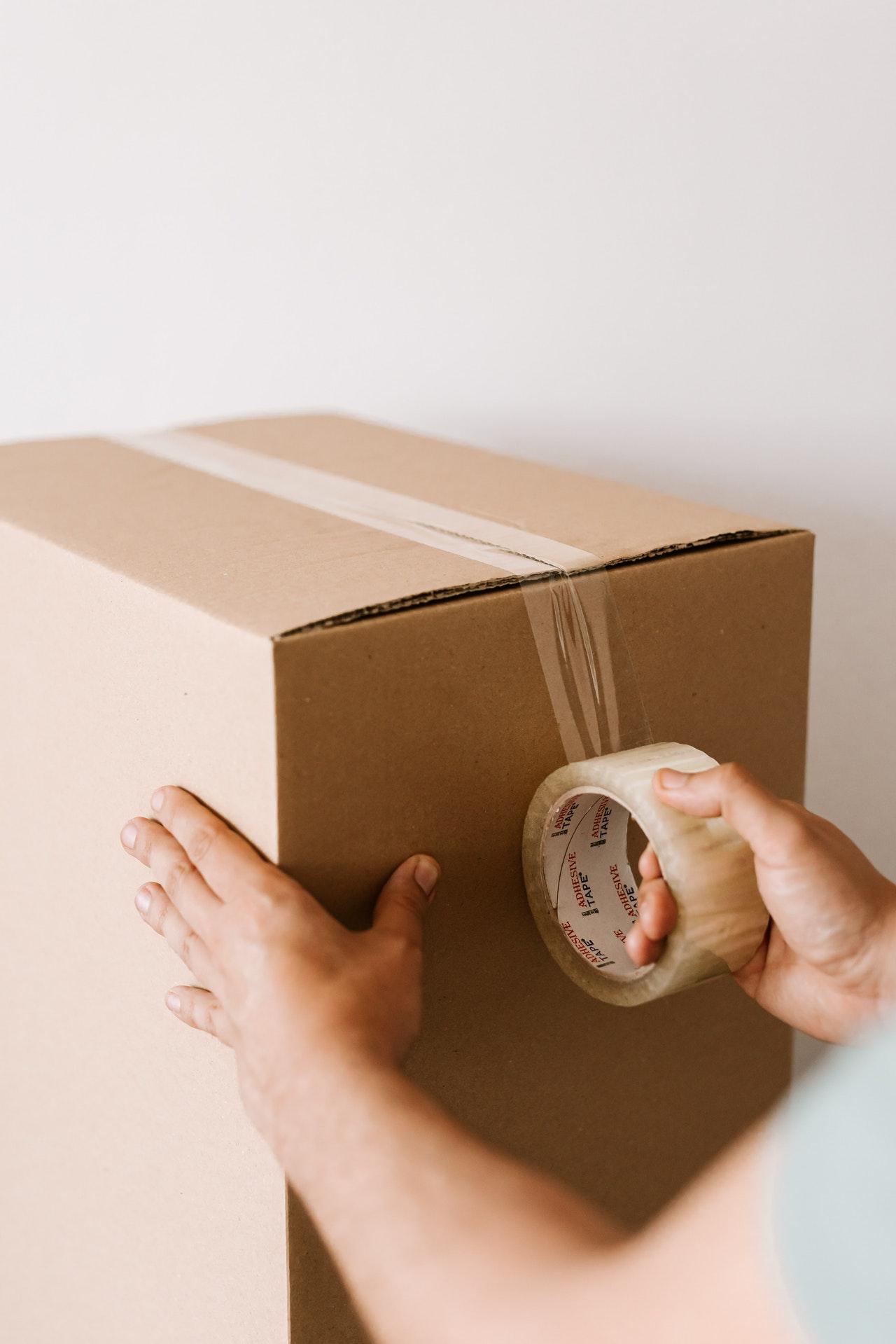 man sealing a moving box