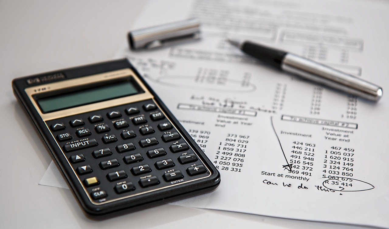 A calculator, a pen, and a paper on which long distance movers calculate costs