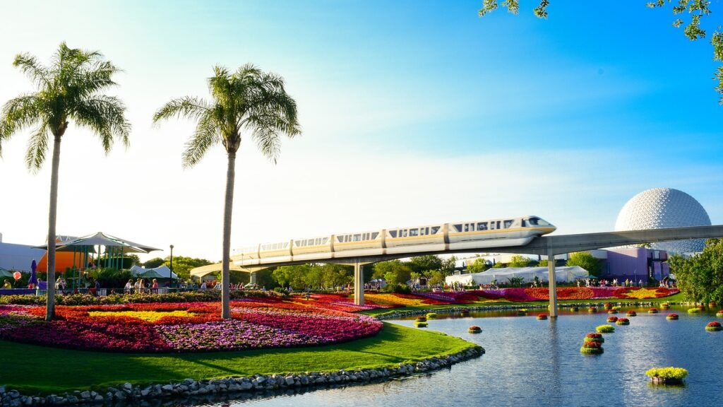 a park with colorful flowers with a train in the background