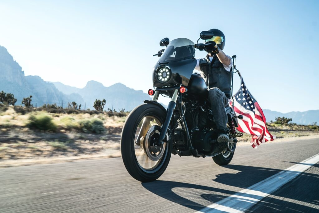 A man riding a motorcycle with an american flag behind him