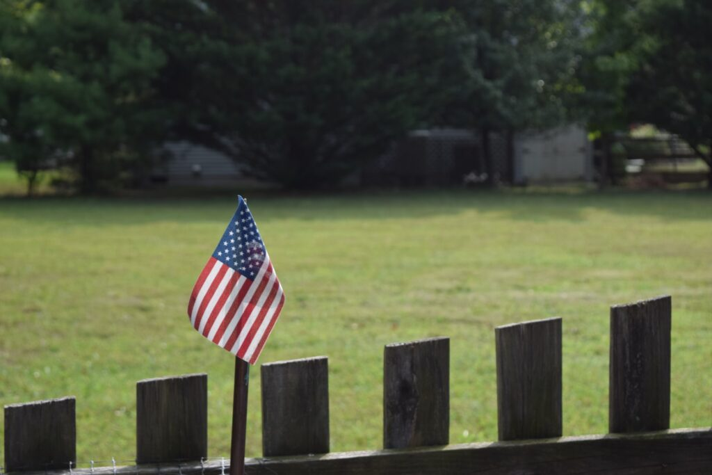 A wooden fence with American flag