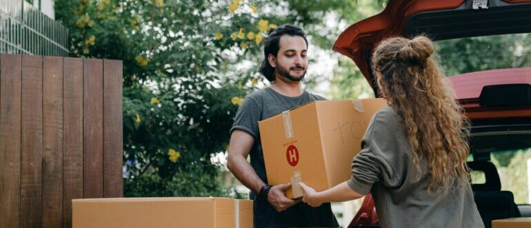 A man helping a woman carry moving boxes